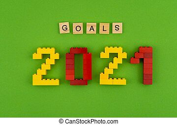 The word goals 2021 is lined with wooden letters on a green background. Figures from the constructor top view. Postcard in place for text. Flatlay. Yellow and red numbers. Copy space.