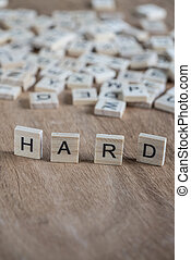 the word hard written with cube letters on wood