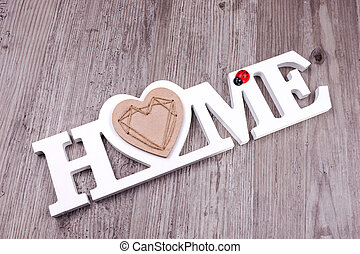 The word Home in on dark wood background