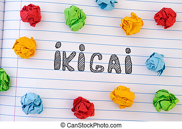 The word Ikigai on notebook sheet with some colorful crumpled paper balls around it