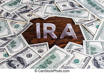 the word ira made of silver metal letters on wooden background surrounded by us dollar banknotes