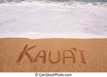 The word Kauai written into the sand in front of surging...