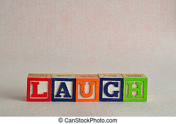 The word laugh spelled with colorful blocks isolated on a white background