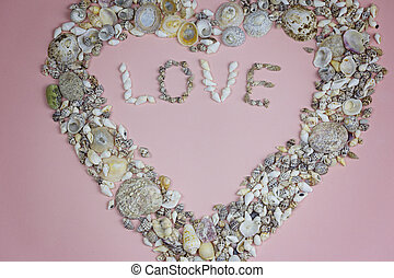 The word love and a heart lined with seashells on a pink background