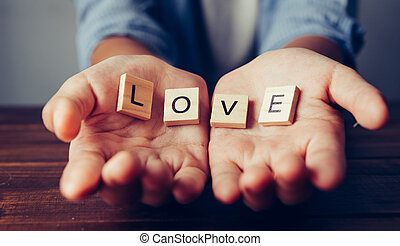 "The word ""LOVE"" in hands in cupped shape. Concepts of sharing, giving,"