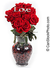 The word love in silver on red roses