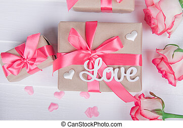 The word love in white letters on gift boxes with pink ribbons. Love concept, Valentine's day