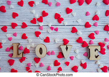 The word love in wooden letters on a background of red, pink, white hearts. Happy Valentine's Day, Mother's Day, March 8, World Women's Day holiday card concept.