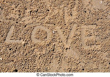 The word LOVE on sand