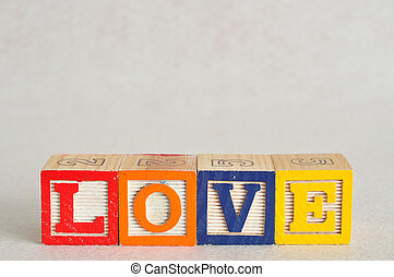 The word love spelled with colorful alphabet blocks isolated on white background