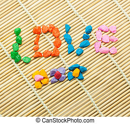The word LOVE spelled with colorful stones