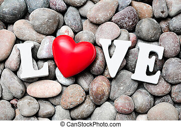 The word Love with red heart on pebble stones