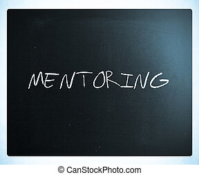 """The word """"Mentoring"""" handwritten with white chalk on a blackboard."""