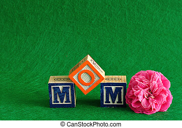 The word mom spelled with alphabet blocks against a green background with a pink flower