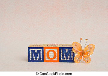 The word mom spelled with alphabet blocks against a white background and a silk butterfly
