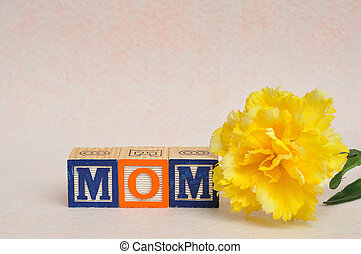 The word mom spelled with alphabet blocks against a white background with a yellow flower