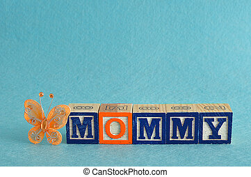 The word mommy spelled with alphabet blocks against a blue background and a silk butterfly