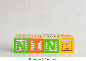 The word nine (9) spelled with colorful alphabet blocks isolated against a white background