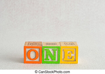 The word one (1) spelled with colorful alphabet blocks isolated against a white background