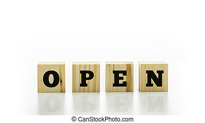 The word Open on four natural wooden cubes