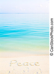 The Word Peace Written in the Sand on a Beach with morning sea background
