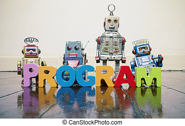 the word PROGRAM with wooden letters and retro toy robots on an old wooden floor