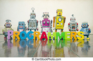 the word PROGRAMMERS with wooden letters and retro toy robots on an old wooden floor