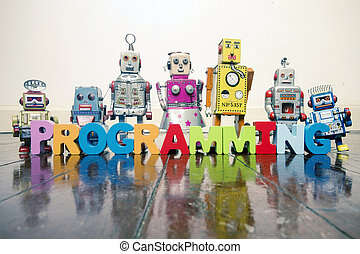 the word PROGRAMMING with wooden letters and retro toy robots on an old wooden floor