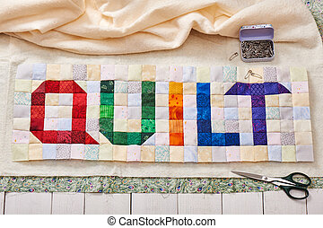 The word quilt sewn from colorful square and triangle pieces...