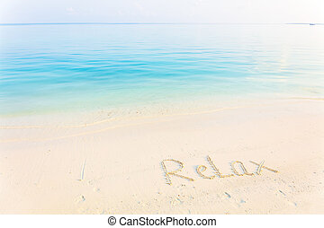 The Word Relax Written in the Sand on a Beach with morning sea background
