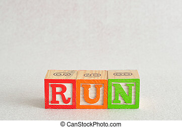 The word run spelled with alphabet blocks isolated on a white background