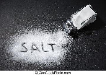 The word salt written into a pile of white salt and salt shaker on black table