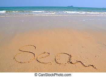 The word Sea is written on a sand background