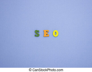 The word SEO on a blue background of wooden multicolored letters.