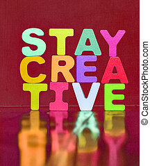 the word STAY CREATIVE  on a red felt background