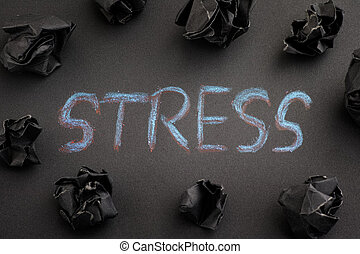 The word Stress with some black crumpled paper balls around it