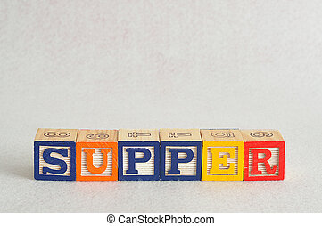 The word supper spelled with alphabet blocks isolated on a white background