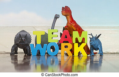 the word TEAM WORK with wooden letters and 5 toy dinosaurs