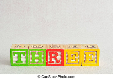 The word three (3) spelled with colorful alphabet blocks isolated against a white background