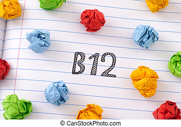 The word Vitamin B12 on notebook sheet with some colorful crumpled paper balls around it