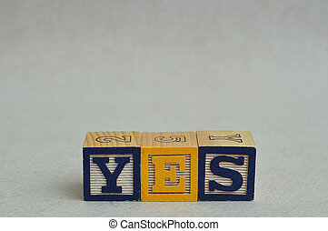 The word yes spelled with colorful alphabet blocks isolated against a white background