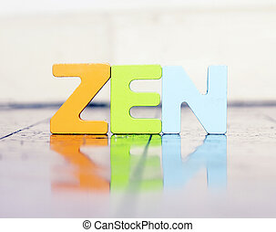 the word ZEN with wooden letters on a wooden floor