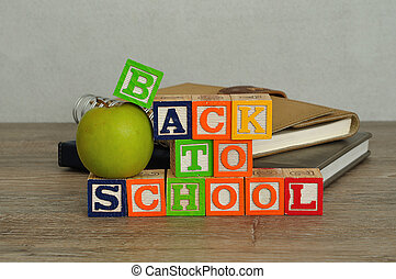 The words back to school spelled with colorful alphabet blocks displayed with a green apple and a stack of books on a table with a white background
