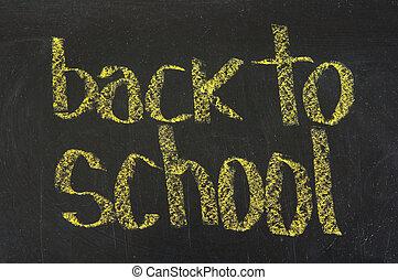 The words 'Back to School' written in chalk on blackboard