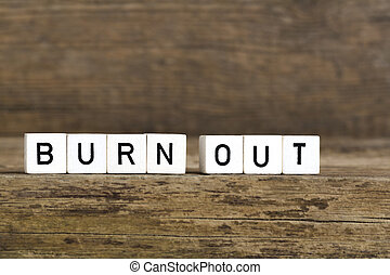 The words burn out written in cubes on wooden background