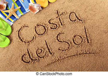 The words Costa del Sol written on a sandy beach with beach towel, starfish and flip flops. Studio shot - directional lighting and warm color are intentional.