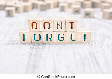 The Words Don't Forget Formed By Wooden Blocks On A White Table, Reminder Concept