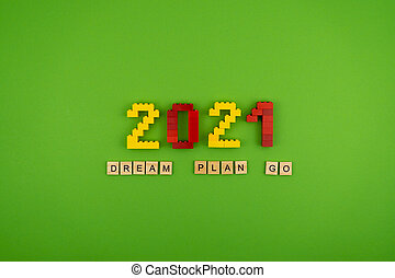 The words dream, plan, go 2021 is lined with wooden letters on a green background. Figures from the constructor top view. Postcard in place for text. Flatlay. Yellow and red numbers. Copy space.