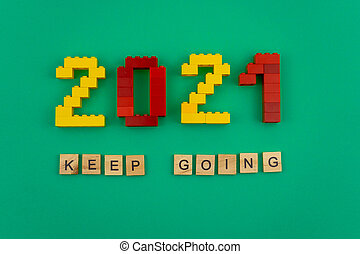 The words keep going 2021 is lined with wooden letters on a green background. Figures from the constructor top view. Postcard in place for text. Flatlay. Yellow and red numbers. Copy space.