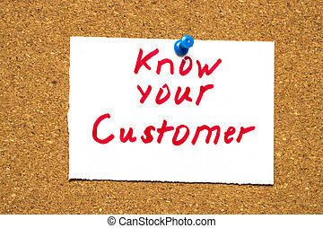 The words Know Your Customer on a note card pinned to a cork notice board